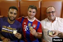 Anthony Sadler, from Pittsburg, California, Aleck Sharlatos from Roseburg, Oregon, and Chris Norman, a British man living in France (L-R), three men who helped to disarm an attacker on a train from Amsterdam to France, pose with medals they received for t