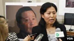 Geng He, istri Gao Zhisheng, berbicara kepada wartawan di depan poster bergambar suaminya. Gao telah hilang selama satu tahun belakangan ini.