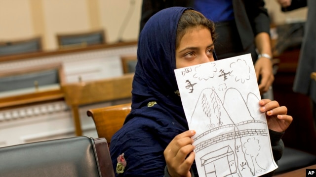 Nine-year-old Nabila Rehman holds a photo with a drawing she made depicting a drone strike that killed her grandmother, Oct. 29, 2013.