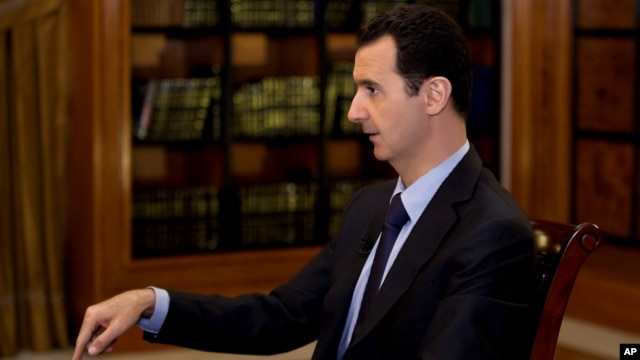 FILE - In this photo, which AP obtained from Syrian official news agency SANA President Bashar Assad gestures as he speaks during an interview on Oct. 21, 2013.
