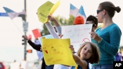 六岁的女孩伊兹和母亲一道加入示威人群,抗议科罗拉多州杰斐逊郡校董会审议历史教纲的计划。(2014年10月4日)