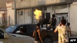 Un membre des forces loyales au Gouvernement libyen soutenu par les Nations Unies (GNA) tire une mitrailleuse près de la zone centrale appelée District One, dans la ville côtière de Syrte, à l'est de la capitale Tripoli, 21 août 2016.