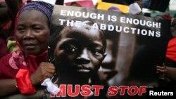 Một người trong đoàn biểu tình cầm biểu ngữ với nội dung phản đối vụ bắt cóc các nữ sinh
