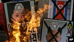 South Korean protesters burn the pictures of North Korean leader Kim Jong Un during an anti-North Korea rally following a nuclear test conducted by North Korea, in Seoul, South Korea, February 12, 2013.