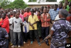 FILE - Policemen stand guard as residents gather at the scene where more than 20 people were killed in their homes in an overnight attack in the Ruhagarika community of the rural northwestern province of Cibitoke, in Burundi, May 12, 2018.