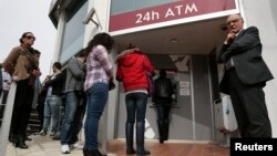 People queue up to make a transaction at an ATM outside a branch of Laiki Bank in Nicosia, March 21, 2013.