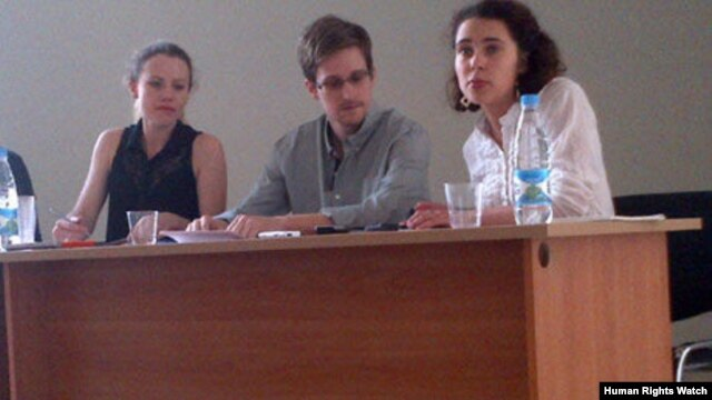 Edward Snowden at the Moscow airport July 12, 2013, with Sarah Harrison of Wikileaks (left).