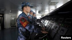 FILE - Chinese naval soldiers are pictured manning their stations on China's first aircraft carrier Liaoning, as it travels towards a military base in Sanya, Hainan province, in this undated picture made available on Nov. 30, 2013.