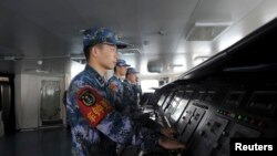 FILE - Chinese naval soldiers are pictured manning their stations on China's first aircraft carrier Liaoning, as it travels towards a military base in Sanya, Hainan province.