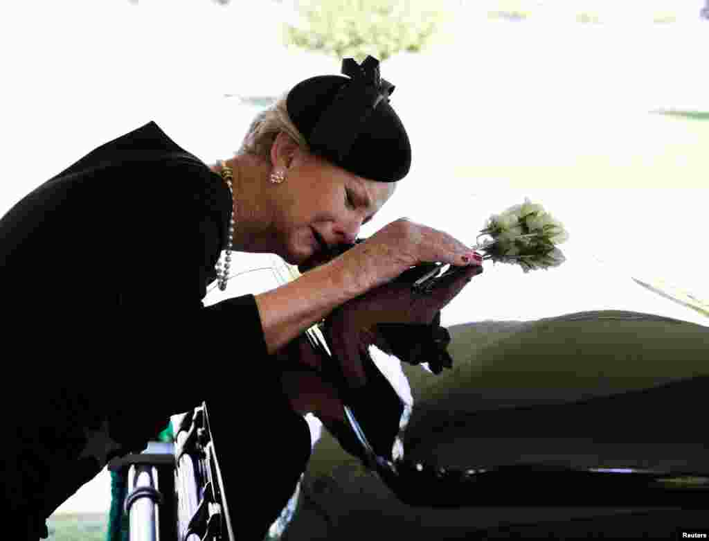 Cindy McCain lays her head on the casket of her late husband Sen. John McCain, R-Ariz., during a burial service at the cemetery at the United States Naval Academy in Annapolis, Maryland, Sept. 2, 2018.