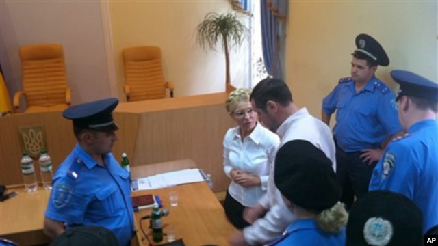 Policemen arrest former Ukrainian Prime Minister Yulia Tymoshenko, center rear, in the Pecherskiy District Court in Kiev, Ukraine, Friday, Aug. 5, 2011