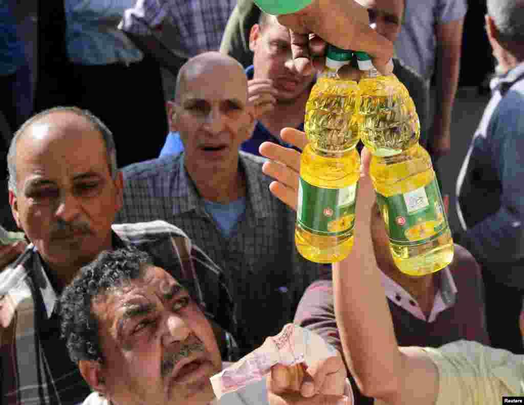 خرید و فروش روغن و دیگر محصولات یارانه ای از یک کامیون دولتی در قاهره مصر. بعد از سرازیر شدن ارزخارجی، توسط بانک مرکزی مصر، خیلی از کالاهای فروشگاههای مواد غذایی کم شدند و باعث شدند که مردم مصر از دولت محصولات یارانه ای بخرند.