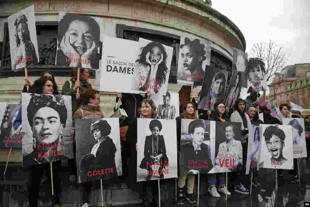 Women hold posters of famous feminists during a gathering to mark International Women's Day in Paris, France.