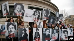 Para perempuan membawa poster para tokoh feminis ternama pada acara untuk merayakan Hari Perempuan Internasional di Paris, Perancis.