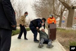 FILE - An officer helps up a drunk man passed out by a trash bin in Poksam County, in northwestern China's Xinjiang Uyghur Autonomous Region, March 21, 2021.