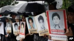 Para kerabat berdemo di luar Kedutaan Besar AS sambil membawa foto para aktivis yang hilang dan korban pelanggaran HAM yang diduga dilakukan oleh sejumlah anggota KOPASSUS pada 1997-1998, 27 Juli 2010. (Foto: Dita Alangkara/AP,arsip)