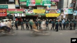 Bangladeshi rickshaw pullers pedal past riot police standing guard in front of the main opposition Bangladesh Nationalist Party (BNP) office in Dhaka, Bangladesh, 29 Nov., 2010.