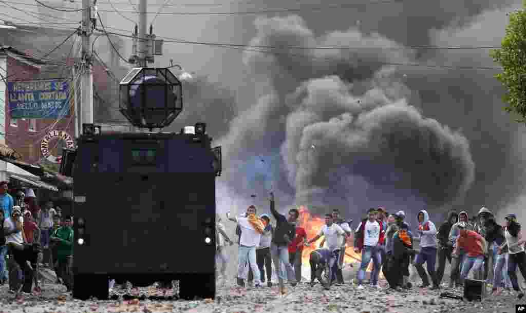 Policijsko vozilo i prosvjednici prilikom bliskog susreta tokom prosvjeda u kolumbijskonm gradu Ubate. Prosvjedi su bili podržka farmerima koji su blokirali ceste tražeći subvencije, manje cijene goriva i poništavanje ugovora o slobodnoj, bescarinskoj trgovini.
