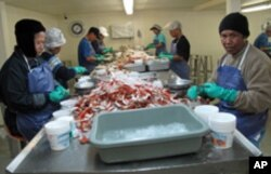 Employees, many from Laos and Thailand, crack crab shells for up to 12 hours a day in Bayou La Batre, Alabama.
