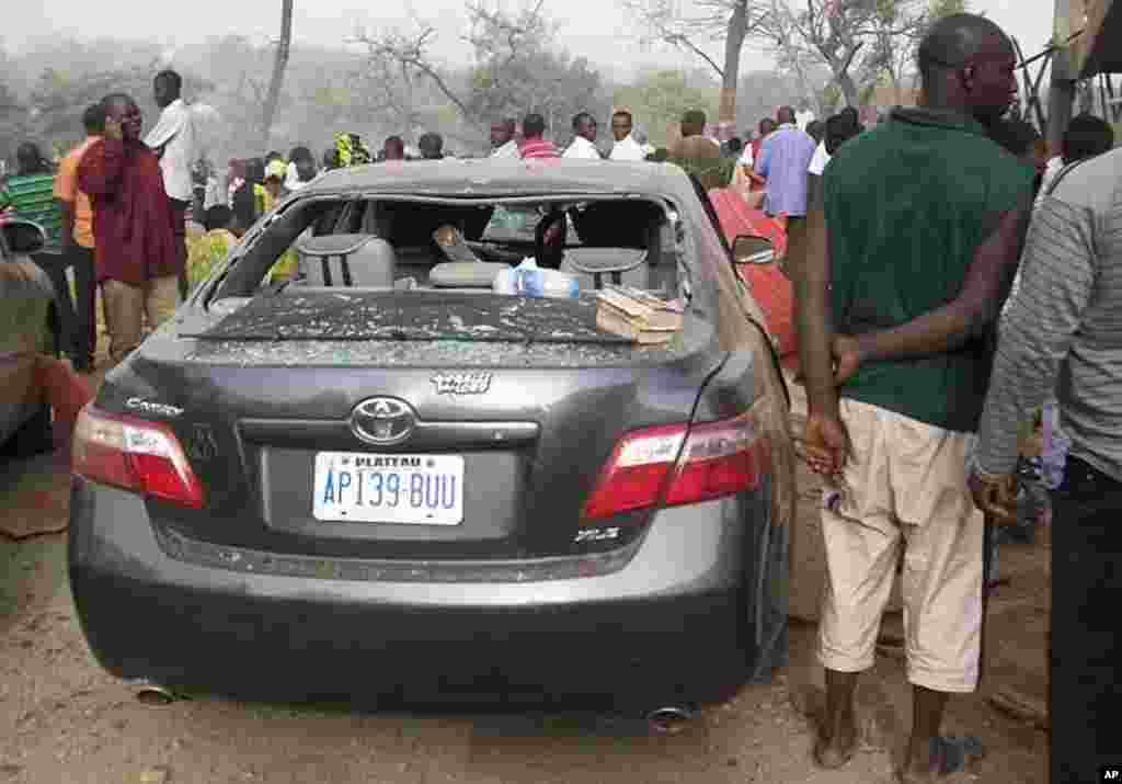 People stand by a damaged vehicle at a church, the site of a bomb blast, in Nigeria's central city of Jos February 26, 2012.