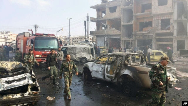 In this photo released by the Syrian official news agency SANA, Syrian citizens gather at the scene where two blasts exploded in the pro-government neighborhood of Zahraa, in Homs province, Syria, Feb. 21, 2016.