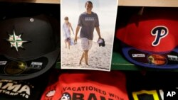 A photograph of President Barack Obama, top, is attached to a shelf near hats and souvenir clothing in a shop, Aug. 6, 2015, in Oak Bluffs, Mass., on the island of Martha's Vineyard.
