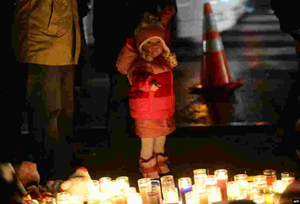 2012年12月16日,人们在一处临时纪念龛凭吊小学枪击案遇难者,一名小孩手指着蜡烛。