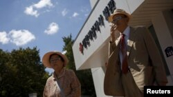 Oh Seong-ik (R), 83, who said he has family members living in North Korea, smokes after preparing documents for reunion, outside the Red Cross building in Seoul, South Korea, September 7, 2015.