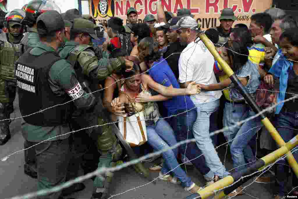 People clash with Venezuelan National Guards as they try to cross the border to Colombia over the Francisco de Paula Santander international bridge in Urena, Venezuela, Dec. 18, 2016.