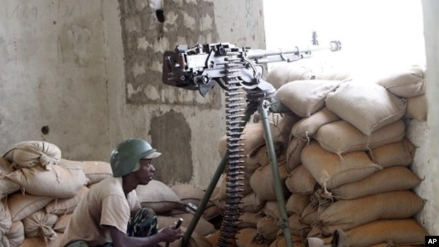 A soldier in the African Union Mission in Somalia (AMISOM) takes his position during fighting between Islamists and government forces in southern Mogadishu, February 14, 2012.
