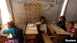 Trẻ em Syria ngồi trong một lớp học tạm thời tại trại tị nạn Bab Al-Salam ở Azaz, tháng 10/2014. Phúc trình nêu ra nhiều yếu tố làm cho trẻ em không thể tới trường, trong đó có những vụ tấn công làm cho trường học bị hư hại hoặc bị phá huỷ, người tị nạn hoặc những kẻ vũ trang dùng trường học làm nơi tạm trú, và phụ huynh giữ con ở nhà vì đường tới trường quá nguy hiểm.