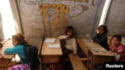 FILE - Children attend a class inside a makeshift school in the Bab Al-Salam refugee camp in Azaz, Syria, Oct. 27, 2014.