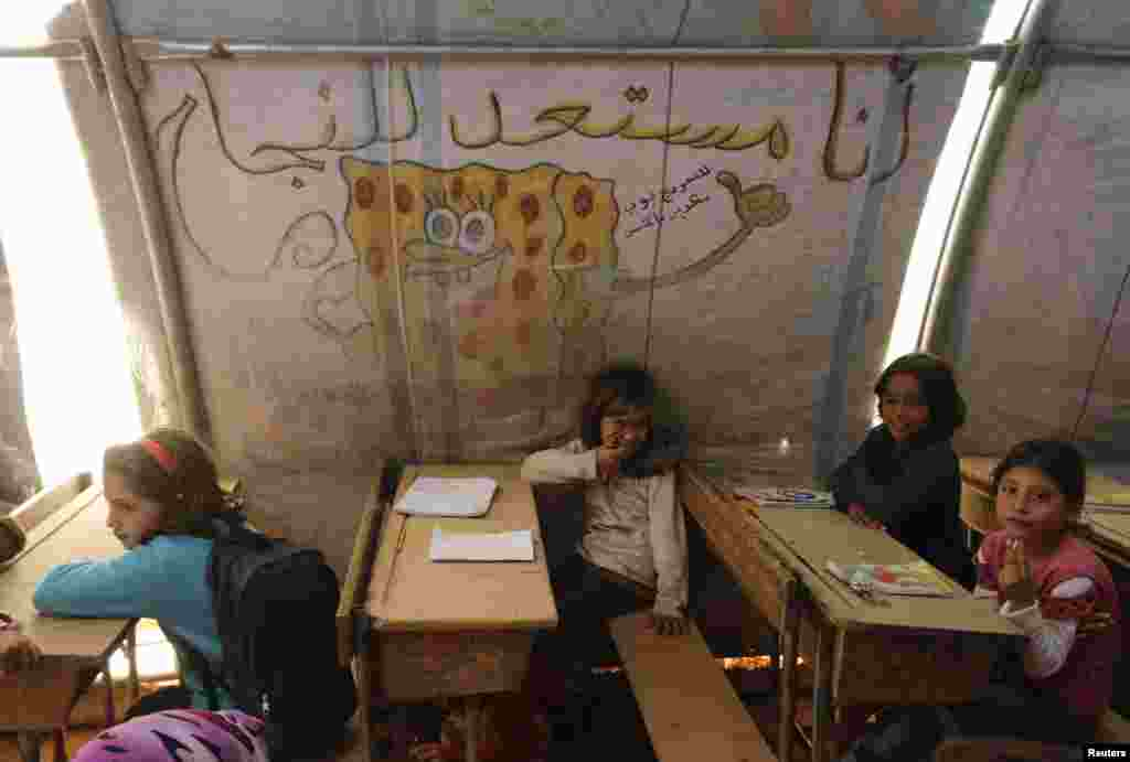 Children attend a class inside a makeshift school in the Bab Al-Salam refugee camp in Azaz, Oct. 27, 2014.