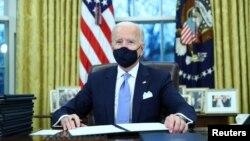 Tổng thống Mỹ Joe Biden kí các sắc lệnh hành pháp trong Phòng Bầu dục của Nhà Trắng ở Washington, sau khi ông nhậm chức tổng thống thứ 46 của Hoa Kỳ, ngày 20 tháng 1, 2021.