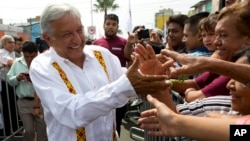 FILE - Presidential hopeful and two-time candidate Andres Manuel Lopez Obrador greets supporters as he arrives at a campaign rally for Delfina Gomez, who is running for Mexico state governor with his National Regeneration Movement, or MORENA, in Nezahualcoyotl, Mexico state, May 28, 2017.