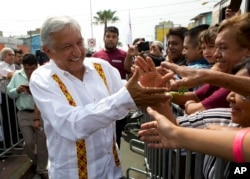 FILE - Presidential hopeful and two-time candidate Andres Manuel Lopez Obrador greets supporters in Nezahualcoyotl, Mexico state, May 28, 2017.