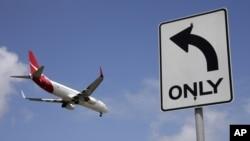 FILE - A Qantas plane prepares to land at Sydney Airport, at Sydney, Australia, Feb. 21, 2013.