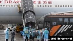 接載港人從武漢撤離的包機3月4日下午返抵香港國際機場。機上港人離開飛機後隨即在身著保護衣的工作人員指示下登上專車前往隔離營。(香港政府新聞處)