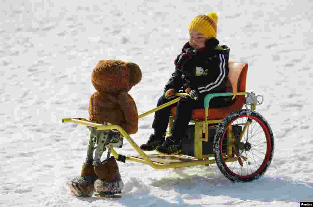 A boy rides on a snow wagon towed by a robot dressed as a Teddy bear during the Ice and snow carnival at Taoranting park in Beijing, China, Feb. 9, 2015.