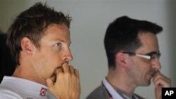 Pebalap Jenson Button, kiri, berdiri di sebelah mekanik tim McLaren (foto: dok.).