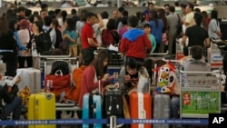 Passengers wait at airline counters at Hong Kong's international airport, Sept. 23, 2013.
