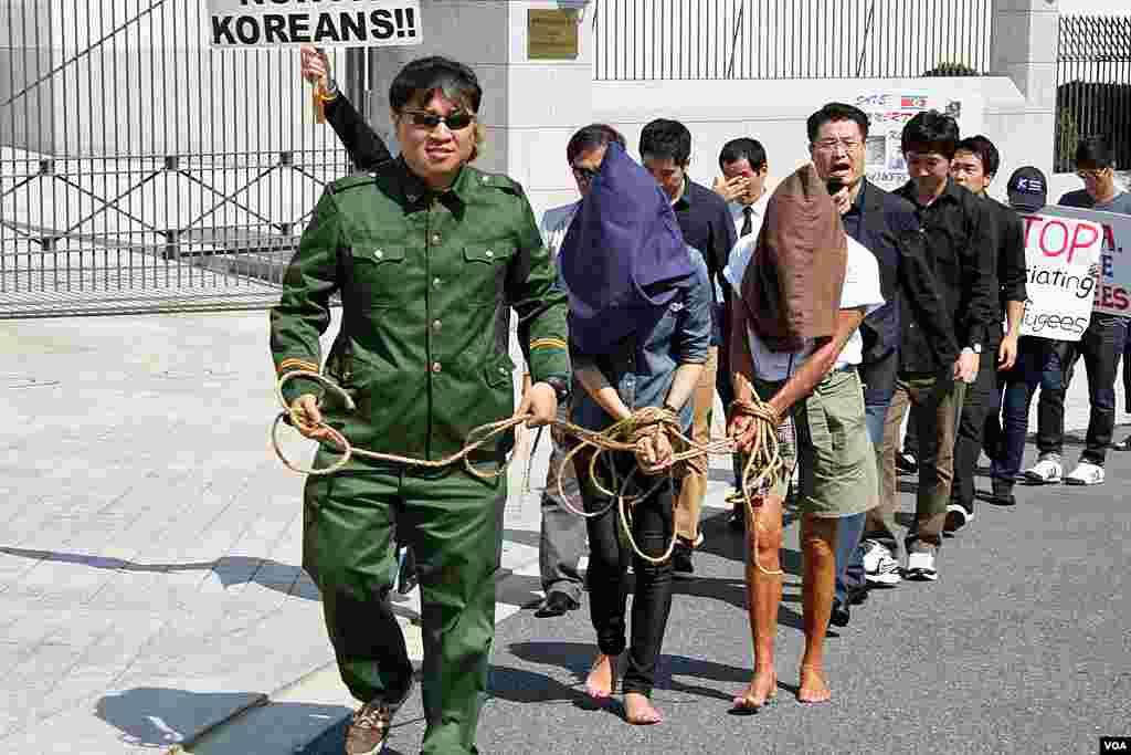 22일 미국 워싱턴 주재 중국대사관 앞에서 중국 정부의 탈북자 강제북송 중단을 촉구하는 시위가 열린 가운데, 중국 공안이 탈북자들을 체포하는 장면을 연출한 퍼포먼스.