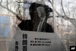 "FILE - A man reading a newspaper posted on a public newspaper bulletin board is reflected on a glass as a photo of U.S. President-elect Donald Trump is published on a Chinese newspaper with an article that reads ""Trump uses fist to talk"" in Beijing, Jan. 3, 2017."
