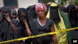 Members of the public gather outside the hospital mortuary, waiting to view the bodies of the alleged attackers, in Garissa, April 4, 2015.