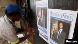 A South African man sells newspapers.