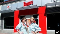 Wendy's Russia workers pose out side of the new restaurant in Moscow, August 2011