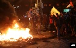 Người biểu tình Palestinian đốt lốp xe trong khi vẫy cờ Palestine và giơ hình của cố Tổng thống Palestine Yasser Arafat trong một cuộc biểu tình tại quảng trường chính ở Thành phố Gaza, ngày 6 tháng 12, 2017.