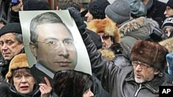 Supporters of Mikhail Khodorkovsky hold his portrait outside a court room in Moscow, 27 Dec 2010