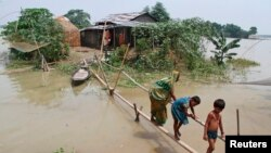 Villagers use a makeshift bamboo bridge to move across flooded areas of Morigaon district in the northeastern Indian state of Assam August 20, 2014.