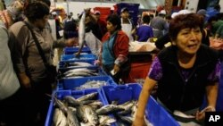 A woman buys fish at the Villa Maria del Triunfo fish market in Lima, Peru. (File)